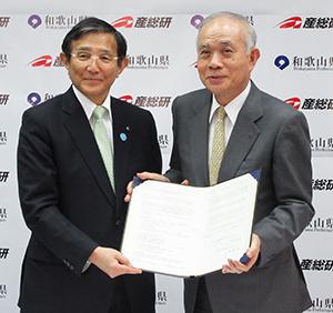 協定書を手にする仁坂知事㊧と中鉢理事長
