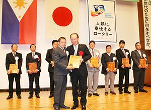 藤本会長(前列右)はじめ各クラブ会長に感謝の盾を手渡すリー会長(同左)
