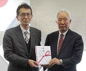 目録を手にする上野山常務理事㊨岡﨑局長
