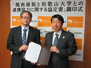 協定書を手にする瀧学長㊨と今村常務理事