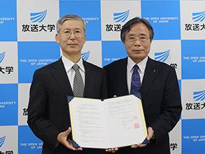 調印を終え協定書を手にする岡村学長㊧と有川理事長