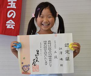認定証とお手玉を手に笑顔の江澤さん