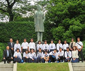 陸奥宗光像の前で記念撮影した生徒ら(加太中学校提供)
