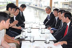 尾花市長(左奥から2人目)らと意見を交わす山本大臣(右手前)