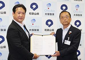 協定書を手にする山本部長㊨と藤原大阪支店長