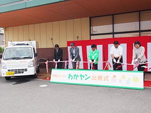 出発式でテープカットを行う井上社長(左から3人目)ら