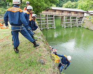 ロープをつたって石垣を降りる消防職員