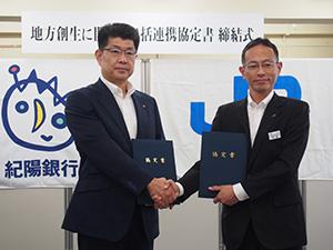 連携協定を締結し、握手を交わす日野執行役員㊧と伊藤支社長