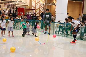 フラフープにボールを投げて遊ぶ子どもたち