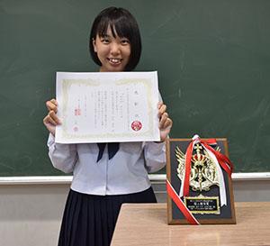 優秀賞の賞状と盾とともに松本さん