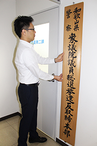 捜査二課の入り口に看板を掲げる県警職員