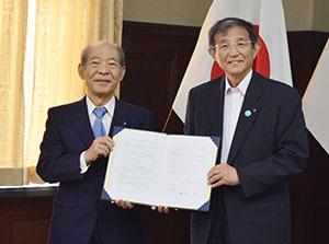 協定書を手に塩﨑学長㊧と仁坂知事