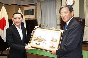 トン委員長㊧から記念の絵を受け取る仁坂知事