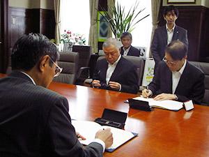 協定書にサインする仁坂知事(手前)と大城学長