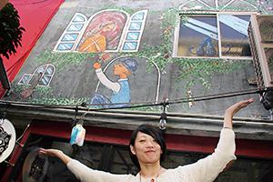 壁画アートの前でmoco mocoさん