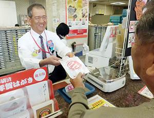 「気を付けてください」と声を掛けながら切手袋を手渡す郵便局員