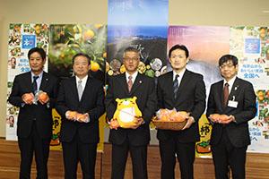 県産柿を手に輸出の拡大を目指す原部長㊨とJA関係者ら