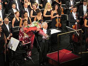 演奏後の拍手の中、花束を手に笑顔を見せる向山さん