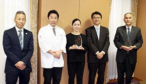 表彰式に出席した佐々木代表取締役㊨と利光社長(右から2人目)、山西部長㊧ら