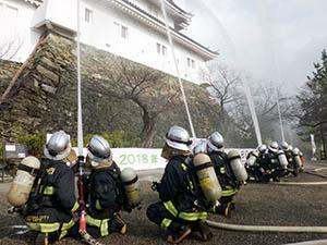 天守閣に向かって一斉放水する消防局員