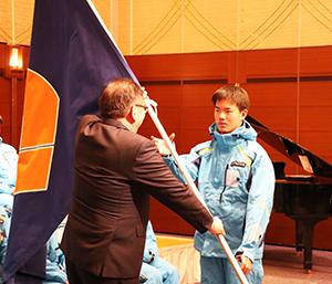 宮下副会長から団旗を受け取る森下選手