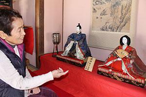 明治時代に作られた人形を見つめる仲井さん
