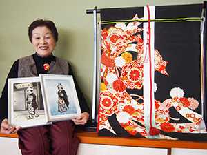 几帳に生まれ変わった留め袖の前で婚礼写真を手にする新谷垣内さん