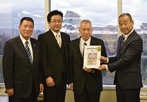 原教育長㊨に文集を手渡した田中さん、出納課長、半田会長(左から)