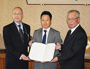協定書を手に(左から)土井局長、桑原社長、中芝市長