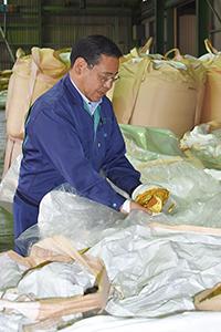 ミカンの皮を発酵させ、乾燥した飼料を手に兼田所長
