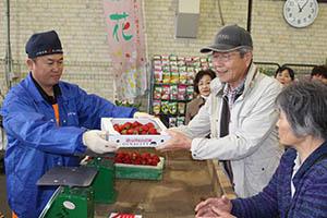 箱入りイチゴを購入する買い物客たち