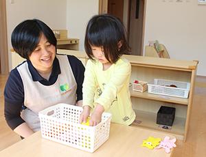 保育士と一緒におもちゃで遊ぶ園児