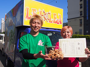 キッチンカーの前で自慢のから揚げと賞状を手にする那須さん夫妻