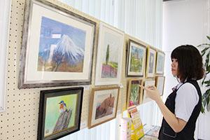 富士山などが描かれたパステル画が並ぶ店内
