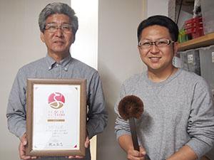 大賞の賞状とボディーブラシを手に髙田社長㊧と大輔専務