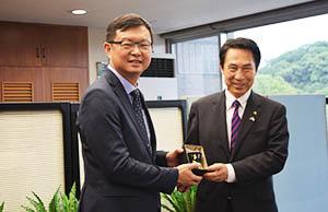 李副主任㊧から記念品を受け取る尾花市長