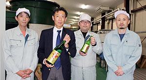商品を手にする雜賀社長(左から2人目)と製造担当の社員ら