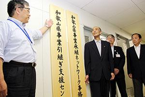事務局入口に看板を設置する野田常任幹事(左から2人目)ら