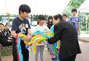 児童から千羽鶴を受け取る衣笠理事長