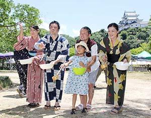 和歌山城を背に水をまく参加者