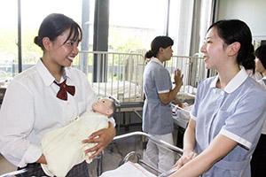 赤ちゃんの人形で抱き方を学ぶ高校生㊧