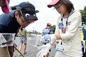 干潟の生き物を調べる子どもと揖学芸員