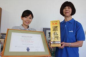 30年連続受賞の日本酒と証書を手に長谷川社長㊨と聡子さん