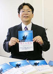 酒を断つまでの体験をまとめた本を手に奥村さん