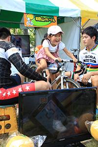 笑顔で競技用自転車をこぐ子ども