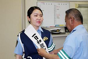 一日警察署長のたすきを掛けてもらう円香さん