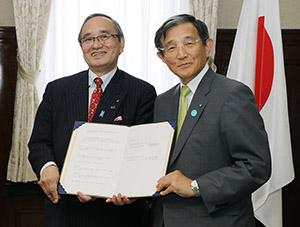 協定書を手に岸野理事長㊧と仁坂知事