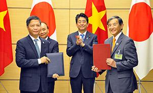 安倍首相が立ち会う中、覚書を手にする仁坂知事㊨とアイン商工大臣(県提供)