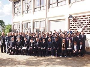 校舎の前で記念撮影した参加者ら