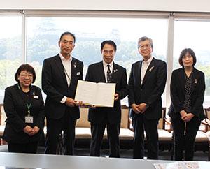 包括連携協定を締結した川腰支社長(左から2人目)と尾花市長ら